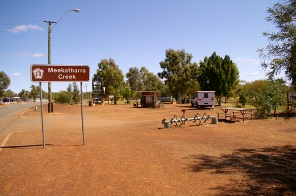The road leading in to Meekathara. The earth is red, with tall trees, a bench and a caravan in the distance. The sign in the left foreground reads 'Meekatharra Creek'.
